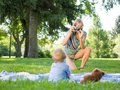 Mother photographing baby boy at park mid adult during picnic Stock Images