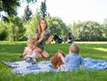 Mother photographing children in park happy mid adult during picnic at Stock Image