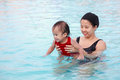 Mother play with daughter in pool Royalty Free Stock Photo