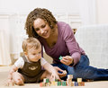 Mother playing with alphabet blocks with her son Stock Photography