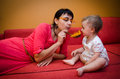 Mother playing with a baby decorative spoon and feather Royalty Free Stock Photo