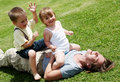Mother playing with children on a lawn Stock Photos