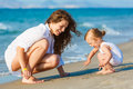 Mother playing with daughter on the beach Stock Photography