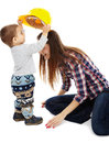 Mother playing with her son little boy putting a construction hardhat on his s head Royalty Free Stock Photo
