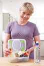 Mother Preparing Healthy Lunchbox In Kitchen Royalty Free Stock Photo