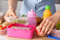 Mother preparing lunch box for her children Royalty Free Stock Images