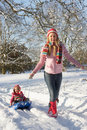 Mother Pulling Daughter On Sledge Through Snow Royalty Free Stock Image