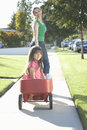 Mother pulling daughter in trolley outdoors rear view of a smiling on pathway Royalty Free Stock Photos