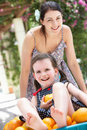 Mother Pushing Daughter In Wheelbarrow Stock Photo
