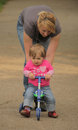 Mother pushing her daughter on a tricycle cute baby girl sitting trike being pushed by Stock Image