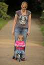 Mother pushing her daughter on a tricycle cute baby girl sitting trike being pushed by Royalty Free Stock Photography