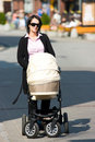Mother pushing pram Royalty Free Stock Image