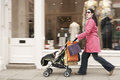 Mother pushing stroller by clothes shop full length side view of young baby Stock Photo