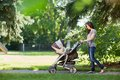Mother pushing stroller in the park full length of young a Stock Photography
