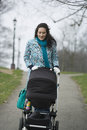 Mother pushing stroller in park happy young walking with baby carriage Royalty Free Stock Images