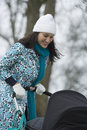 Mother pushing stroller in park happy young walking with baby carriage Royalty Free Stock Photo