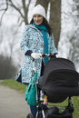 Mother pushing stroller in park happy young woman walking with baby carriage Royalty Free Stock Photos