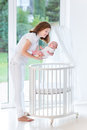 Mother putting her newborn baby to sleep in crib young a white round Stock Image