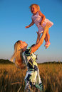 Mother raises child on hands in wheaten field Royalty Free Stock Photo