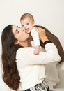 Mother raising baby and play, happy family portrait on white background, yellow toned Royalty Free Stock Photo