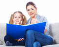 Mother reading book with daughter at home isolated Stock Image