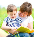 Mother is reading book for her child while sitting on a green grass outdoors Royalty Free Stock Photos
