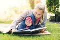 Mother reading a book to baby in backyard garden on blanket Royalty Free Stock Photo