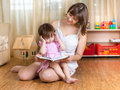 Mother reading a book to her kid daughter Stock Image