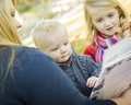 Mother reading a book to her two adorable blonde children wearing winter coats outdoors Royalty Free Stock Photography