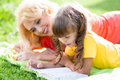 Mother reading a book to kid outdoors in summer Royalty Free Stock Photo