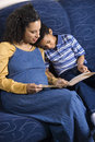 Mother Reading Book to Son Stock Images