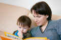 Mother reading with her son on the sofa Stock Images