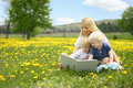 Mother reading story book to two young children outside in meado a happy is sitting a meadow of yallow dandelion flowers a her Royalty Free Stock Images