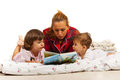 Mother reading story to kids her in bed before sleep Stock Photography