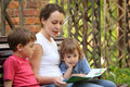 Mother reads book for children sits on bench Stock Photo