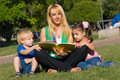 Mother reads to children of the book on a glade in Royalty Free Stock Photography