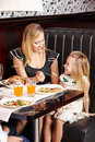 Mother in restaurant letting a her daughter taste new food from her plate Stock Photo