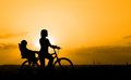 Mother riding on a bicycle with her child silhouette of backlit by sunset Stock Photo