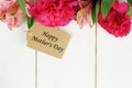 Mother's Day gift tag with flowers on white wood Royalty Free Stock Photo