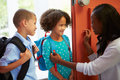 Mother saying goodbye to children as they leave for school smiling at each other Stock Images