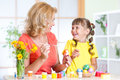 Mother showing to her child how to paint Easter