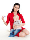 Mother with sick baby young thermometer and sit on a white background Stock Photography