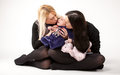 Mother and sister kissing lithe baby on floor young at studio Stock Image