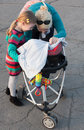 Mother and sister playing peek a boo with his baby brother sitting in a stroller on walk an autumn park Stock Images