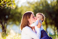 Mother sitting on the grass kissing her little son green sunny nature Royalty Free Stock Photo
