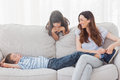Mother sitting with her children on sofa at home in living room Royalty Free Stock Image