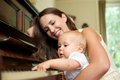 Mother smiling as baby plays piano portrait of a Royalty Free Stock Photography