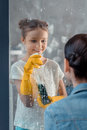 Mother and smiling daughter in protective gloves washing window
