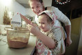 Mother smiling and tutoring her daughter in the kitchen as she is preparing dough for homemade christmas cake family values Royalty Free Stock Photos