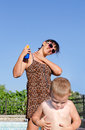 Mother and son applying suntan lotion her young to their skin to protect against ultraviolet rays as they prepare to spend the hot Royalty Free Stock Photos